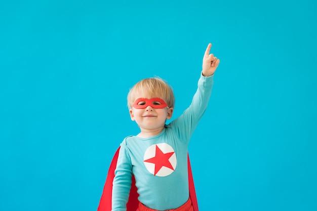スーパーヒーローの子供の肖像画。青い壁に対してスーパーヒーローの子供。