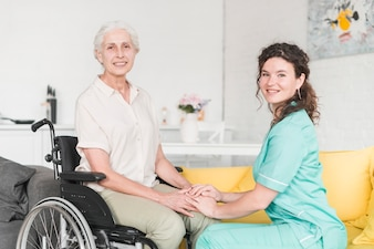 Portrait of supportive smiling nurse with senior female patient sitting on floor