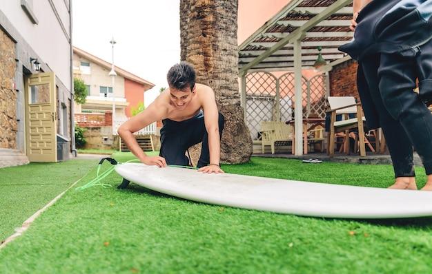 美しい女性のウェットスーツワックスがけサーフボードを持つサーファー男の肖像画。夏のスポーツのコンセプト。