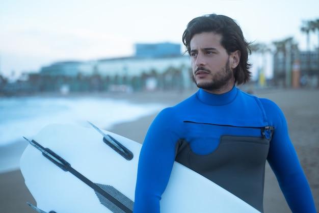 サーフィンの準備ができている海を見ている彼のサーフボードを立って保持しているサーファーの肖像画