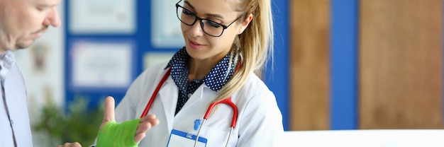 弾性包帯で手の包帯を作る外科医の肖像画。医師による診察の男性。医療制服を着た看護師。ヘルスケアと予防の概念