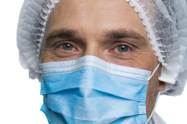 外科医の顔の肖像画。白い壁に隔離された呼吸マスクの医師の顔の拡大図。