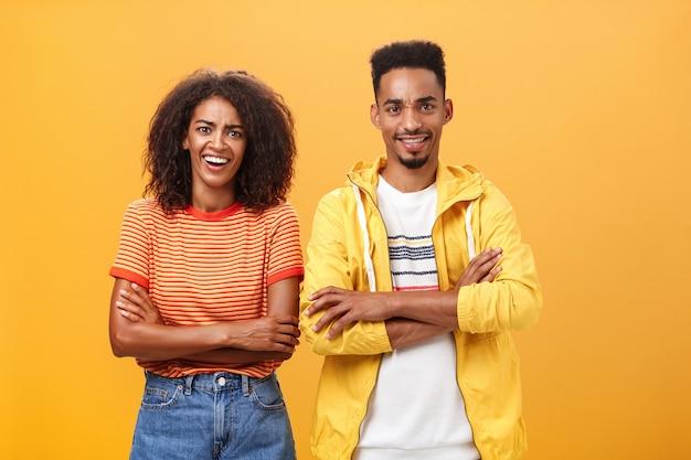 胸に腕を組んで立っているアフロの髪型を持つ驚いたアフリカ系アメリカ人のカップルの肖像画。