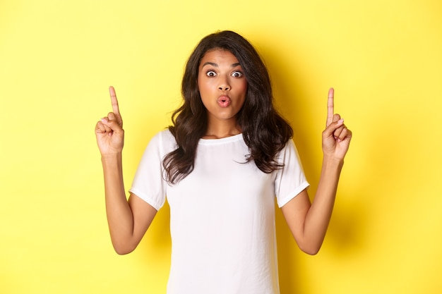 Портрет удивленной и взволнованной афро-американской девушки, говорящей «вау» и указывающей пальцем на удивительное промо-предложение, демонстрирующей логотип на пространстве для копирования, стоящей на желтом фоне.