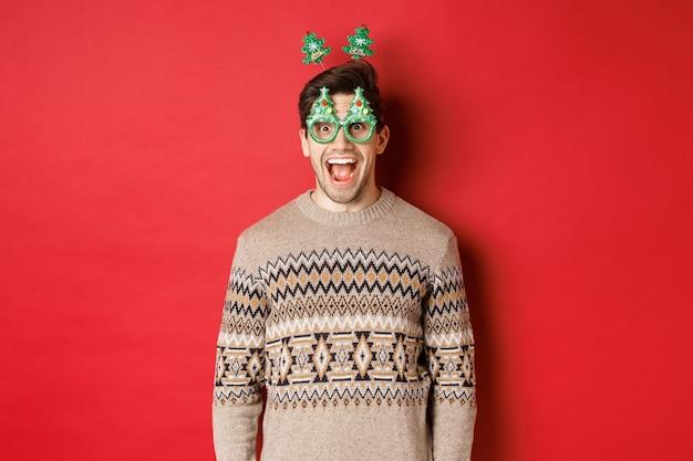 赤い背景に立って、クリスマスを祝って楽しんで、パーティーグラスと冬のセーターで驚いて興奮したハンサムな男の肖像画