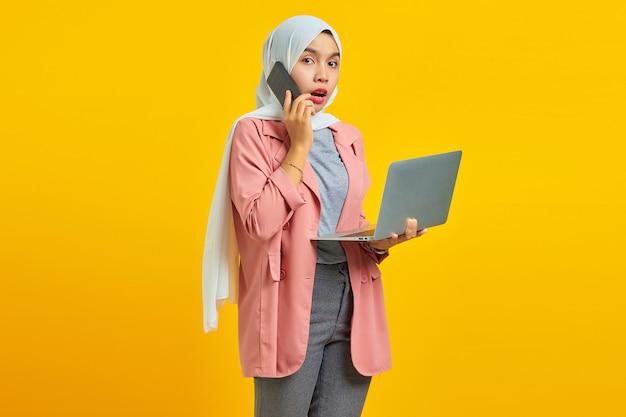 노란색 배경에 격리된 은색 노트북을 들고 스마트폰으로 이야기하는 놀라고 충격을 받은 아시아 여성의 초상화