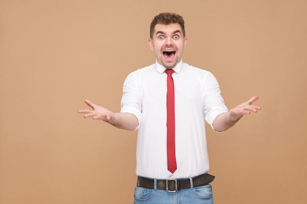 Портрет удивленного и потрясенного человека с открытым ртом. концепция деловых людей, хорошие и плохие эмоции и чувства. студийный снимок, изолированные на светло-коричневом фоне