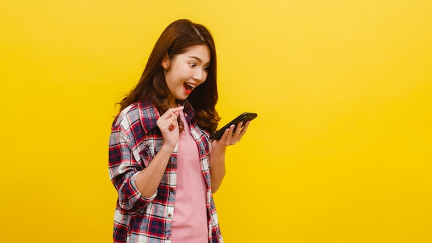 Портрет удивленной азиатской женщины используя мобильный телефон с положительным выражением, одетый в вскользь одежду и смотрящ камеру над желтой стеной. счастливая прелестная радостная женщина радуется успеху.
