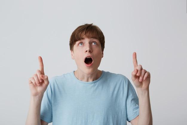 Портрет удивленного, изумленного молодого человека с открытым ртом в синей футболке удивлен и указывает на пространство с обеими руками, изолированными над белой стеной.