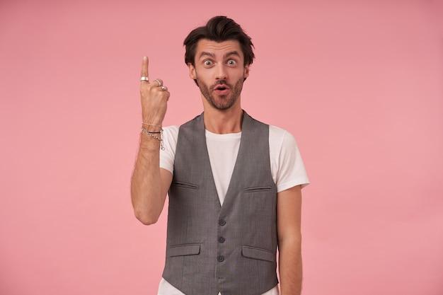 회색 양복 조끼와 분홍색 배경 위에 서있는 흰색 티셔츠에 놀란 수염 난 어두운 머리 남성의 초상화, 넓은 입으로 카메라를보고 집게 손가락으로 위쪽으로 표시