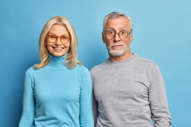 놀란 수염 남자와 중년 금발의 행복 한 여자의 초상화 서로 밀접하게 서 파란색 스튜디오 벽 위에 절연 캐주얼 점퍼를 착용