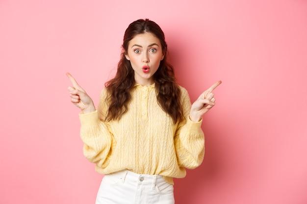 Портрет удивленной девушки-брюнетки, задыхающейся, говорящей «вау» с впечатленным лицом, указывающей в сторону пальцами и двумя копиями, стоящих у розовой стены.