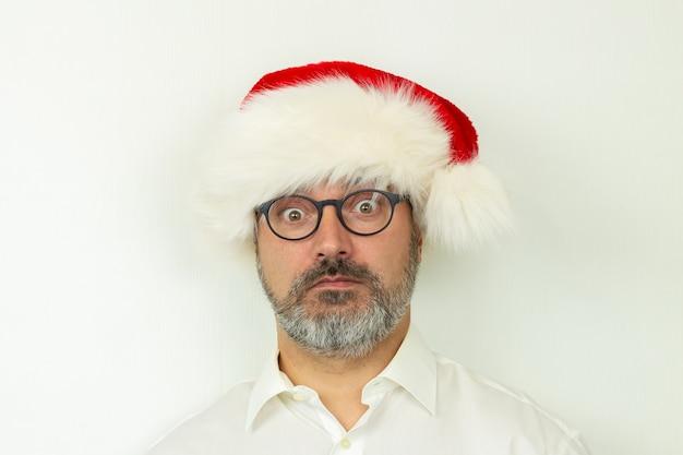 Портрет удивленного бизнесмена в новогодней шапке на белом