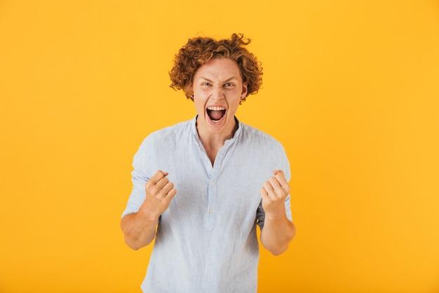 Портрет удивленного веселого человека, кричащего и сжимающего кулаки, изолированного на желтом фоне