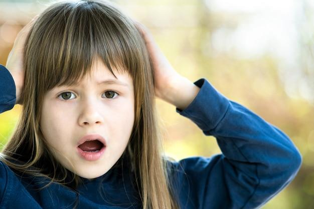 夏の屋外で彼女の頭に手を繋いでいる驚いた子少女の肖像画。外の暖かい日にショックを受けた女性の子供。