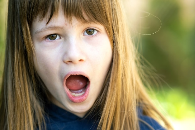 Портрет удивленной девушки ребенка на открытом воздухе летом. потрясенный ребенок женского пола в теплый день на улице.