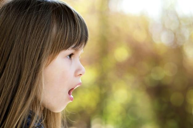 夏の屋外で驚いた子供の女の子の肖像画。外の暖かい日にショックを受けた女性の子供。
