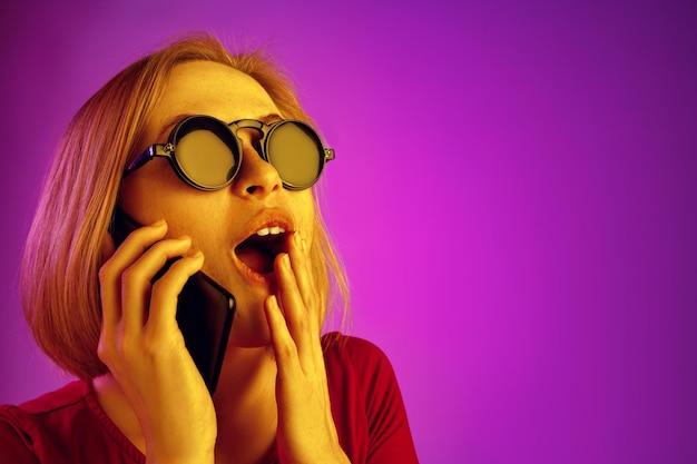 ピンクのネオンの背景に分離された携帯電話を見て驚いた混乱した女性の肖像画