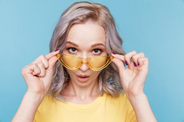 カメラのポーズと青い壁に立っている黄色いメガネを持って驚いたかわいい女の子の肖像画