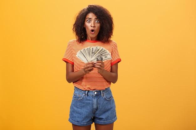 お金を持ってあえぎながら巻き毛の散髪折り唇を持った驚いた浅黒い肌の女性の肖像画。