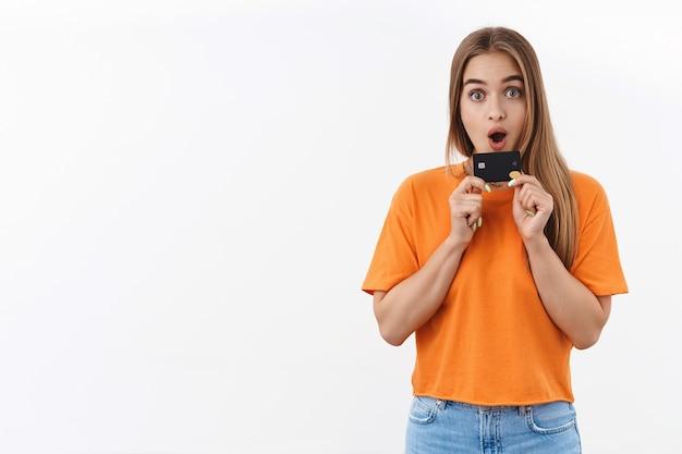 オレンジ色のtシャツを着た驚いた、興奮したブロンドの女の子の肖像画は、夏休みの新しいドレスにすべてのお金を無駄にするのを待つことができません、クレジットカードを持って、感動したカメラを見つめ、オンラインショッピング