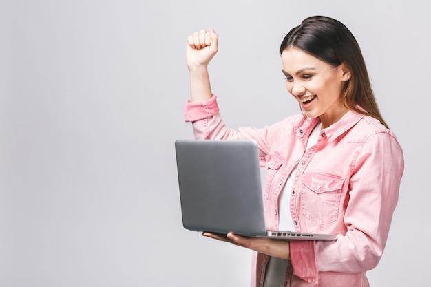 Портрет удивленной взволнованной улыбчивой руки держится, смотрящий на экран ноутбука, изолированный по белому фону,
