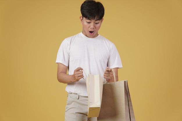 놀란 흥분된 젊은 아시아 남자의 초상화는 부담없이 절연 쇼핑백을 여는 옷을 입고