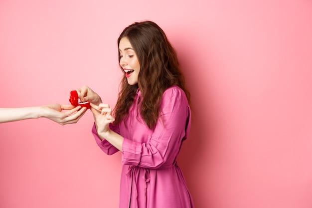 놀란 여자 친구의 초상화는 약혼 반지로 손을보고 놀라움과 흥분의 비명을 지르며 결혼 제안을받습니다.