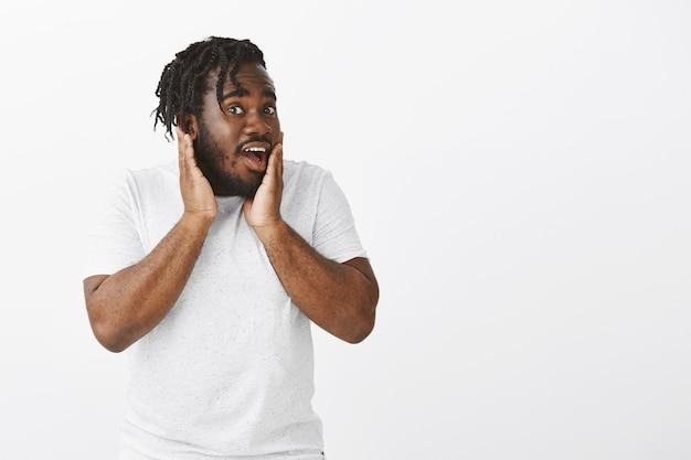 Портрет удивленного парня с косами, позирующего на фоне белой стены