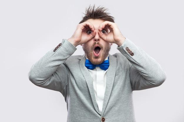 カジュアルな灰色のスーツに驚いたハンサムなひげを生やした男の肖像画、双眼鏡で立っている青い蝶ネクタイは目に手をジェスチャーし、カメラを見ています。明るい灰色の背景に分離された屋内スタジオショット。