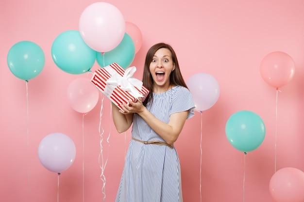 밝은 분홍색 배경에 선물 선물과 화려한 공기 풍선이 있는 빨간 상자를 들고 파란 드레스를 입은 놀란 행복한 여성의 초상화. 생일 휴가 파티, 사람들은 진심 어린 감정 개념입니다.