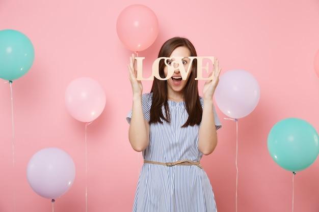 カラフルな気球とパステルピンクの背景に木製の単語の文字の愛を保持している青いドレスで驚いた幸せな若い女性の肖像画。誕生日の休日のパーティー、人々の誠実な感情の概念。