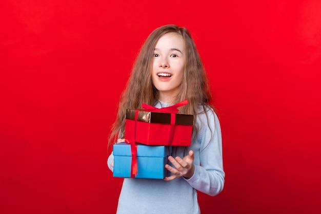 빨간 벽에 선물 상자를 들고 놀란 어린 소녀의 초상화