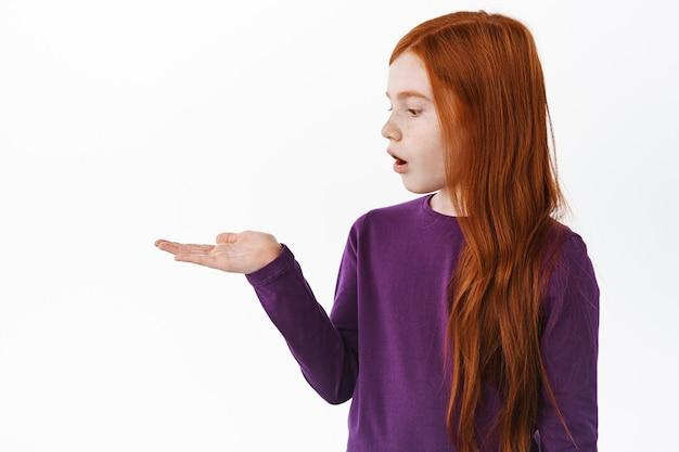 Портрет удивленной маленькой рыжеволосой девушки смотрит на ее ладонь, держа в руке copyspace предмета, и изумленно смотрит, стоя над белой стеной