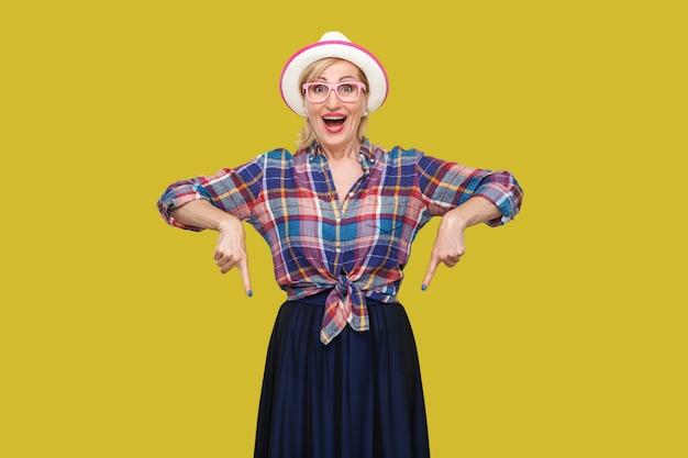 Портрет удивленной современной стильной зрелой женщины в повседневном стиле с стоячей шляпой и очками, пораженной смотрящей в камеру и направленной вниз. крытая студия выстрел, изолированные на желтом фоне.
