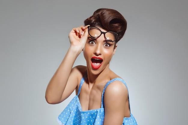 Портрет удивленной женщины в стиле пин-ап в очках