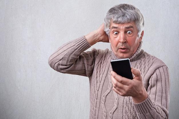 彼の携帯電話で見たものにショックを受けている彼の電話に大きく開いた目で見ている驚いた年配の男性の肖像画。人間の顔の表情。驚き、驚き、不思議