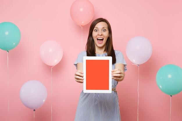 カラフルな気球とパステルピンクの背景に空白の空の画面でタブレットpcコンピューターを保持している青いドレスで驚いたショックを受けた若い幸せな女性の肖像画。誕生日の休日のパーティーのコンセプト。