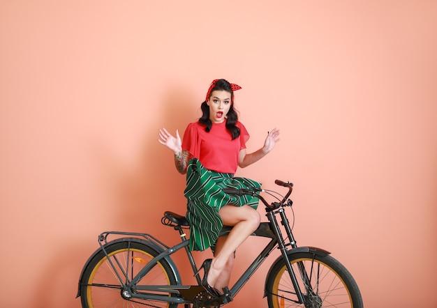 Портрет удивленной татуированной женщины пин ап, катающейся на велосипеде на цвете