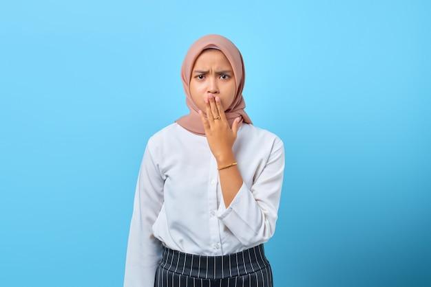 青い背景の上の手で口を覆う驚いた若いアジアの女性の肖像画