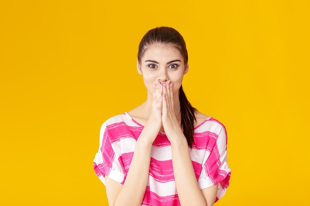 ピンクのシャツの女の子がカメラを見て驚いた若いブルネットの女性の肖像画