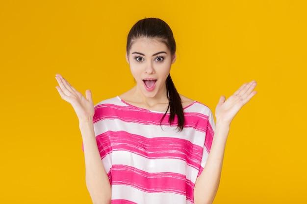 ピンクのシャツで驚いた若いブルネットの女性の肖像画