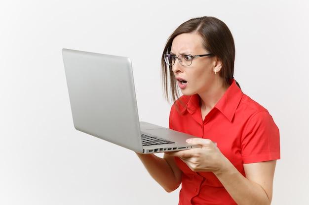 Портрет удивленного молодого пользователя женщины учителя бизнеса в красной рубашке, очках работая печатая на портативном компьютере пк изолированном на белой предпосылке. образование или преподавание в концепции университета средней школы