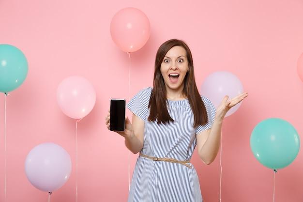 カラフルな気球とパステルピンクの背景に手を広げて空白の空の画面で携帯電話を保持している青いドレスで驚いた若い幸せな女性の肖像画。誕生日の休日のパーティーのコンセプト。