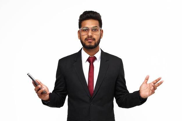 白い孤立した背景に携帯電話で驚いた若いインドのビジネスマンの肖像画。