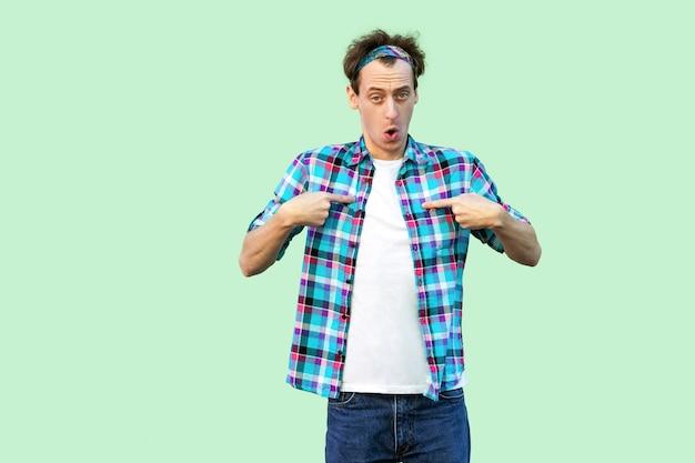 Портрет удивленного молодого человека в повседневной синей клетчатой рубашке и повязке на голову, указывающего на себя и смотрящего в камеру с изумленным лицом. закрытый студийный снимок, изолированные на светло-зеленом фоне