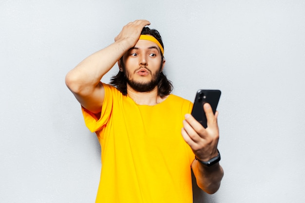 テクスチャード加工の白い壁の背景に黄色のシャツを着てスマートフォンで見て驚いた若い男の肖像画。