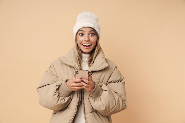 Портрет удивленной молодой женщины в зимнем пальто, улыбающейся и использующей мобильный телефон