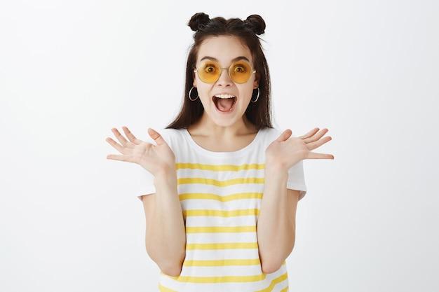 Портрет удивленной молодой женщины, позирующей в солнечных очках на белой стене