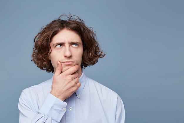 何かを考えながら顔に触れるカジュアルなシャツを着た不審な物思いにふける若い男性の肖像画